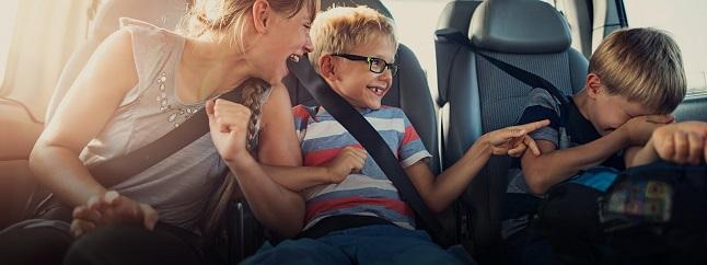 3 Kinder lachend im Auto